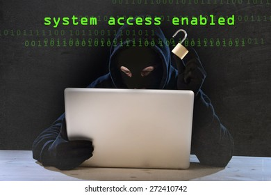 hacker man in black hood and mask with computer laptop holding lock in dangerous dark look hacking system having access to data info and privacy in business digital crack and cyber crime concept