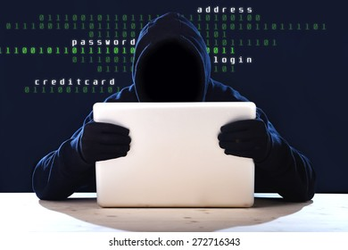 hacker man in black hood and mask with computer laptop in dangerous dark look hacking system having access to data info and privacy in business digital intruder and cyber crime concept