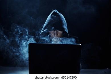 A hacker on a dark background, a computer hacker in the haze