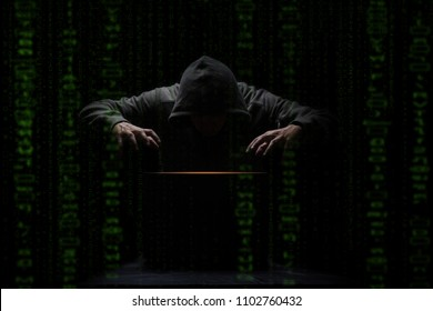 hacker over a screen with green binary code. Crime and Information Theft and Computers