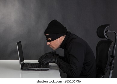 Hacker stealing data from a laptop on black background