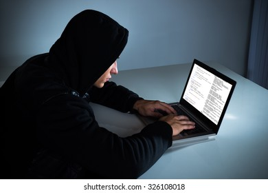 Hacker Stealing Information From Laptop At Desk