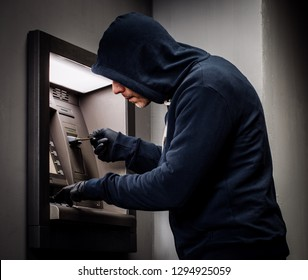 Hacker stealing password and identity on atm machine. Computer crime concept.
