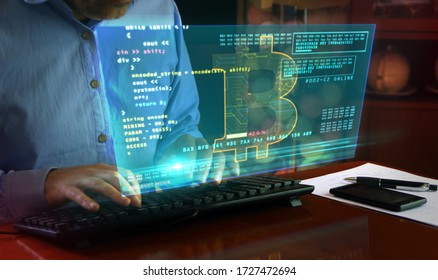 Hacker typing on the keyboard and Bitcoin mining on hologram screen on desk. Digital crypto currency, cyber money and digital banking concept.