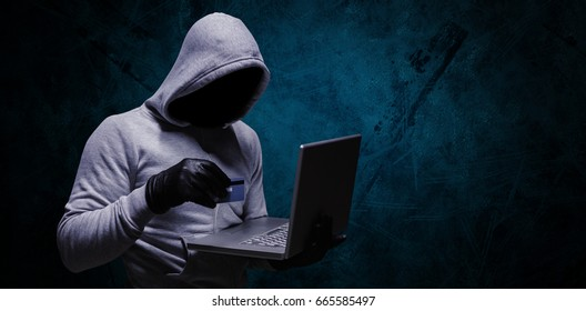 Hacker using credit card for cyber crime against dark background