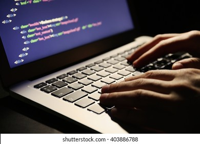 Hacker using laptop, closeup