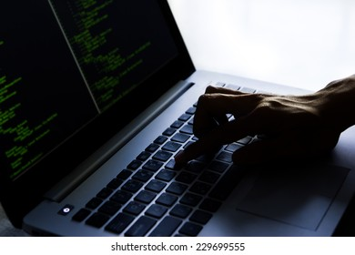 Hacker using laptop in dark room.