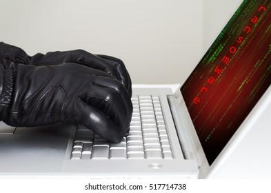 Hacker wearing black gloves using a laptop preparing to attack using ransomware
