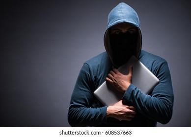 Hacker wearing hood in dark room