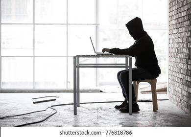 Hacker working in hideaway place and using labtop, concept for computer crimes and internet illegal action