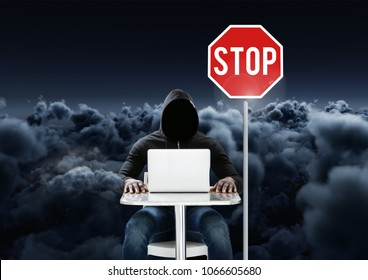 Hacker working on laptop close to a stop board in front of cloudy background