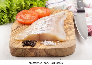haddock fillet with tomato, pepper and coarse salt on a wooden board