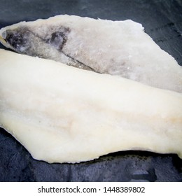 Haddock fillets of fish on a black slate
