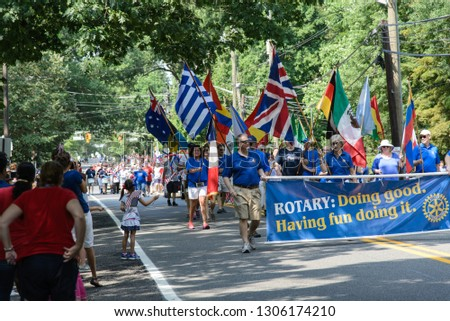 Haddonfield, NJ - July 4, 2018: At a fourth of July parade, the local Rotary club carry flags of the world and a banner reading 'Doing good. Having fun doing it.'