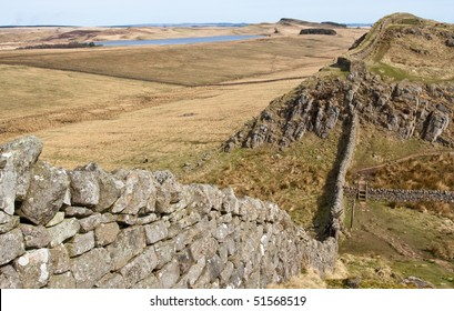 Hadrians wall dipping down the hill and up the other side on a rocky outcrop