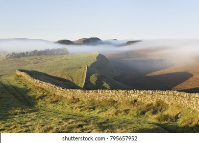 Hadrian's Wall: an early morning autumnal view looking west from King's Hill towards Kennel Crags and Housesteads Roman Fort and Crags. Beyond, Highshield and other crags are shrouded in mist.