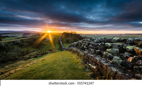 Hadrian's Wall on Walltown Crags at sunset with dramatic clouds.