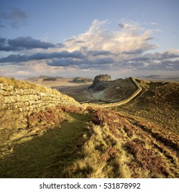 Hadrian's Wall snakes its way across the landscape in Northumberland, England, illuminated by a pastel winter sunset