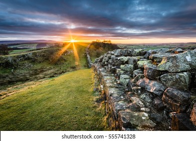 Hadrian's Wall at Walltown Crags as sun sets on the horizon.