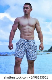 Hagatna, Guam (U.S. Territory) - November 24, 2018: Male fitness model and NPC competitor Joel Atenta models board shorts from the brand Quiksilver during a photo shoot with photographer Darron Bruce.