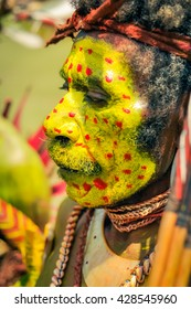 Hagen show, Papua New Guinea - circa August 2015: Old native man with moustache and face covered in yellow colour with red dots during Hagen show, Papua New Guinea. Documentary editorial.