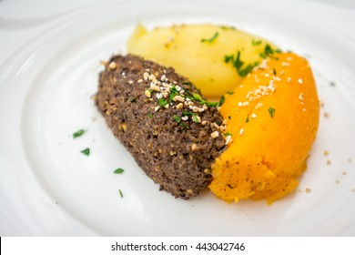 Haggis is a traditional Scottish dish. It is a savoury pudding containing animal's pluck (heart, liver and lungs), commonly served with neeps, and tatties. The animal can be sheep or venison.