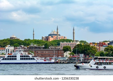 Hagia Sophia and Beautiful View touristic landmarks from sea voyage on Bosphorus. Cityscape of Istanbul at sunset - old mosque and turkish steamboats, view on Golden Horn.