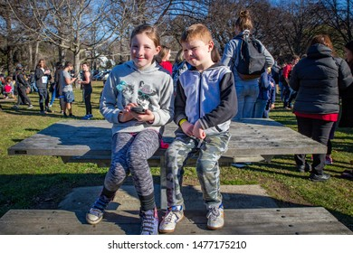 Hagley Park, Christchurch Canterbury, New Zealand, July 16 2016: Children share a smartphone at a community day in the park not long after the launch of the augmented reality game, Pokemon Go