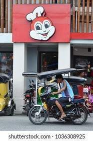 Hagonoy, Bulacan, Philippines -  February 11, 2018: Tricycle driver drives fast in front of Jollibee store.
