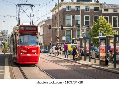THE HAGUE (DEN HAAG), NETHERLANDS. July 19, 2017. Red city tram in the downtown Hague with passengers waiting for public transportation at the bus and tram station.