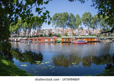 The Hague/ Den Haag, Netherlands - May 30 2009 : houseboats in full color on a canal in the city of The Hague with trees around.