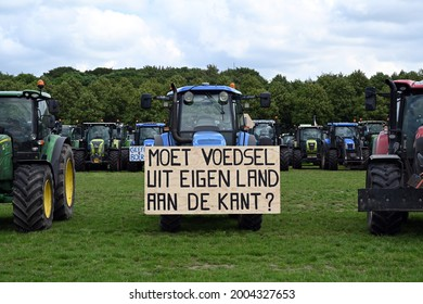 """The hague, Holland - July 7, 2021: A tractor on Malieveld, The Hague with the text """"Moet voedsel uit eigen land aan de kant?"""". English tranlation is """"Does home-grown food have to be put aside?""""."""