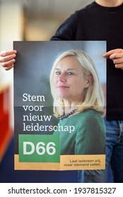 "The hague, Holland - March 17, 2021: A man holding a election poster of dutch political party D66. The text says ""Stem voor nieuw leiderschap. Laat iedereen vrij, maar niemand vallen"". English transla"