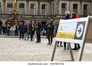 """The hague, Holland - March 17, 2021: People standing in line waiting to vote for the polling station. The text on the sign reads """"Den Haag Stembureau"""". English translation is """"The Hague polling statio"""