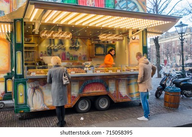 The Hague, the Netherlands - 26 November 2016: people buying fresh oliebollen at a street vendor in The Hague