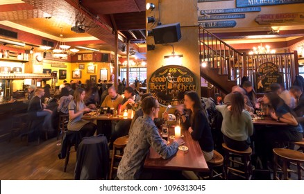 HAGUE, THE NETHERLANDS - APR 6: Men and women having dinner and drinking beer in bar with vintage furniture and decorations on April 6, 2018. Hague is one of major cities hosting the United Nations