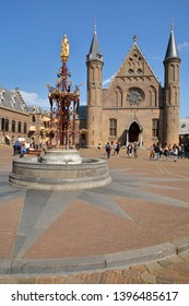 THE HAGUE, NETHERLANDS - APRIL 18, 2019: The Ridderzaal (Knight's Hall), which forms the center of the Binnenhof, with the neo-gothic fountain and the golden statue of King Willem 2 in the foreground