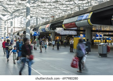 The Hague, The Netherlands - August 6, 2017: Central Train Station The Hague with travelers in the great glass hall with the train platforms and trains.