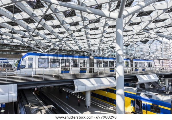 The Hague, The Netherlands - August 6, 2017: Central Train Station The Hague with construction, train, HTM tram, platforms and glass windows.