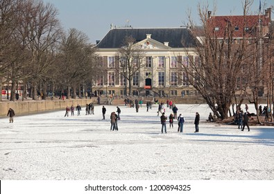 The Hague, The Netherlands - February 10, 2012: People are ice skating on the Hofvijver, court pound of Binnenhof, in front of the historic museum of the Hague