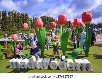 HAGUE, NETHERLANDS - JULY 25, 2017: Tourist attraction miniature park Madurodam in The Hague. Children jumping in playground with giant tulips and inscription Madurodam made of white letters