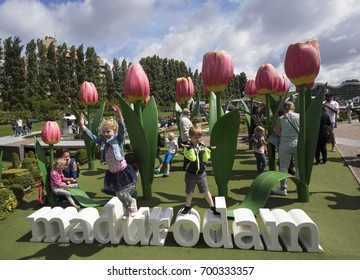 HAGUE, NETHERLANDS - JULY 25, 2017: Tourist attraction miniature park Madurodam in The Hague. Jumping children in playground with giant tulips and inscription Madurodam