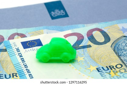 The Hague, The Netherlands - March 1, 2016: A little green car on a blue envelope of the Dutch Tax Authorities with twenty euro notes. Concept for motor vehicle taxes