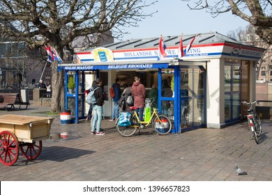 The Hague / The Netherlands - March 2019.  A typical and famous Dutch herring stand / kiosk with customers near Binnenhof, the Dutch parliament, in the Hague.