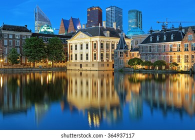 The Hague, Netherlands. The Mauritshuis on the shore of Hofvijver Pond (Court Pond) on the background of the city's skyscrapers in the evening.
