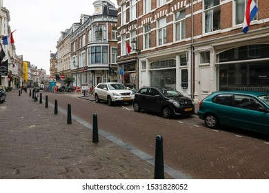 The Hague, The Netherlands - October 07, 2019: Along a narrow street in the old part of the city cars have been parked. On this cloudy day there is rather no visible traffic.