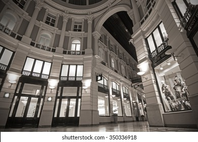 THE HAGUE, THE NETHERLANDS - OCTOBER 3, 2015: Monochrome image of the indoor shopping arcade 'De Passage' (The Hague, The Netherlands) at night, with shop windows illuminated by artificial light.