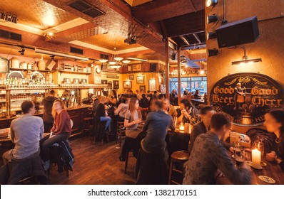 HAGUE, THE NETHERLANDS: People drinking and eating snacks inside old pub with beer taps, vintage furniture and decorations on April 6, 2018. Hague is one of major cities hosting the United Nations