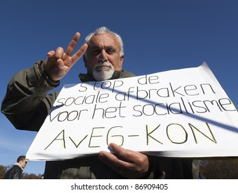 THE HAGUE – OCTOBER 15: An unidentified member of the European Confederation of oppressed immigrants holding a banner, gives a victory sign during the Occupy protest on October 15, 2011 in The Hague, The Netherlands.
