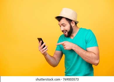 Ha-ha! So funny! Portrait of happy excited crazy man with stubble wearing hat and green tshirt, he is pointing on his smartphone and rejoicing